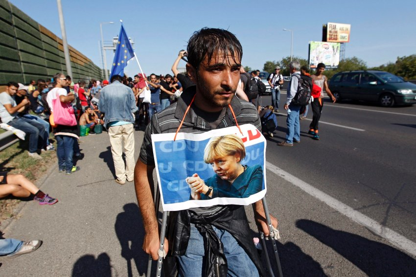 One of the migrants with german Chancelor Merkel's photo on his neck walks out of Budapest, Hungary, 04 September 2015. Several thousand migrants left the Keleti station this afternoon heading for Germany on foot. Hundreds of migrants on 03 September rushed the platforms in Budapest after Hungarian police opened the city's Keleti station, which had been blocked to migrants since 01 September. Hungary's railway service said there were no trains headed to Western Europe for the time being. Thousands of refugees - many of whom have traveled from Africa and the Middle East in the hopes of reaching countries like Germany and Sweden - have been stranded at the station. EPA/ZSOLT SZIGETVARY HUNGARY OUT +++(c) dpa - Bildfunk+++